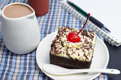 Chocolate cake with cherry and milk jug, notebook. On plate mat Royalty Free Stock Photo