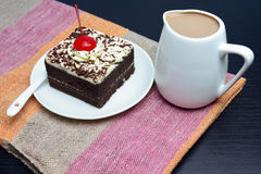 Chocolate cake with cherry and milk jug. On plate  mat Stock Image