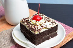 Chocolate cake with cherry and milk jug. On plate  mat Royalty Free Stock Photo