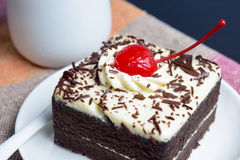 Chocolate cake with cherry and milk jug. On plate  mat Royalty Free Stock Photos