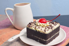 Chocolate cake with cherry and milk jug. On plate  mat Royalty Free Stock Images