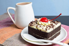 Chocolate cake with cherry and milk jug. On plate  mat Royalty Free Stock Photography