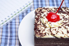 Chocolate cake with cherry and notebook. On plate mat Stock Images