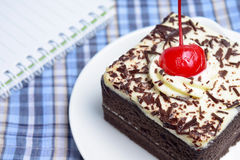 Chocolate cake with cherry and notebook. On plate mat Stock Photo