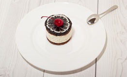 Chocolate cake with cherry on the top icing Royalty Free Stock Images