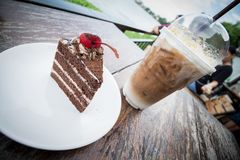 Chocolate cake with cherry topping and ice coffee mocha royalty free stock images