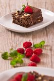 Chocolate cake. Chocolate cake with raspberries on white dish stock photo