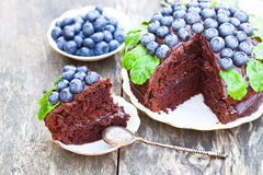 Chocolate  cake with chocolate cream and fresh blueberries and m. Int leaves Stock Photos