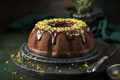 Chocolate  cake with chocolate glaze and pistachios. Chocolate bundt cake with chocolate glaze and pistachios Royalty Free Stock Photo