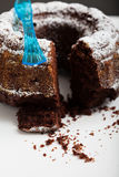 Chocolate cake. Closeup of dry chocolate cake with piece cut out sprinkled with icing sugar and blue plastic fork stock photography