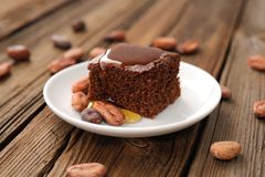 Chocolate cake with cocoa beans and honey. On wooden background Royalty Free Stock Images
