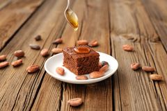 Chocolate cake with cocoa beans and honey. On wooden background Royalty Free Stock Photos