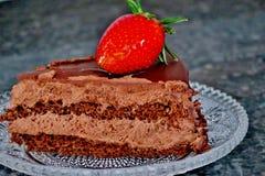 Chocolate cake with cocoa cream and strawberries stock photo