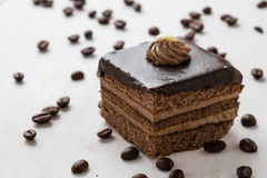 Chocolate cake and coffee beans on table Royalty Free Stock Images