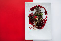 Chocolate cake on contrast colorful background. Of red and white. Delicious dessert serving in restaurant with decoration from cherry, almond and mint, top view Stock Photography