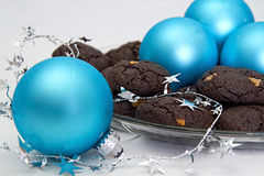 Chocolate Cake Cookies. Holiday chocolate cake cookies with peanut butter chips. Served on glass plate with blue Christmas ornaments an silver garland royalty free stock image