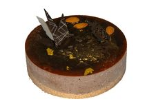 Chocolate cake covered with chocolate mousse and decorated with almonds and gold stock images