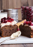 Chocolate cake with cream cheese, raw cherry on white plate. Teaspoon in cream, steel cup, glass Royalty Free Stock Photos