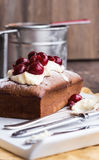 Chocolate cake with cream cheese, raw cherry on white plate. Teaspoon in cream, steel cup, strainer Royalty Free Stock Photo