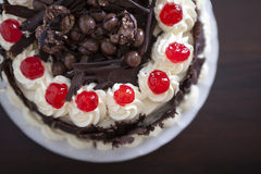 Chocolate cake with cream and cherries. Chocolate cake with cream and cherries on top Stock Photography
