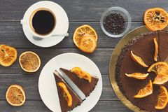 Chocolate cake with cream and profiterole. Decorated with candied oranges top view. Traditional creamy dessert with coffee cup, copy space Royalty Free Stock Photography