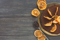 Chocolate cake with cream and profiterole. Decorated with candied oranges top view. Traditional creamy dessert, copy space Royalty Free Stock Image