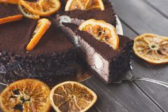 Chocolate cake with cream and profiterole. Decorated with candied oranges. Traditional creamy dessert, copy space Stock Images