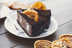 Chocolate cake with cream and profiterole. Decorated with candied oranges. Traditional creamy dessert, copy space Royalty Free Stock Image