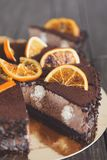 Chocolate cake with cream and profiterole. Decorated with candied oranges. Traditional creamy dessert, copy space Royalty Free Stock Photo