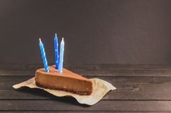 Chocolate cake with cream and three candles Royalty Free Stock Photos