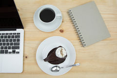 Chocolate cake, cup of coffee and blank notebook. Top view of chocolate cake, cup of coffee and blank notebook Royalty Free Stock Photography