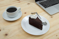 Chocolate cake and cup of coffee on wooden table. Closeup chocolate cake and cup of coffee on wooden table Royalty Free Stock Photos