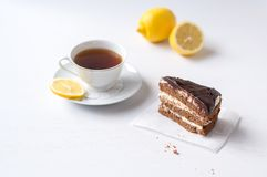 Chocolate cake with a cup of tea. Chocolate cake with a cup of tea on a white background Royalty Free Stock Photo
