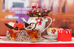 Chocolate cake, cup tea, gift and bouquet roses on kitchen. royalty free stock photography