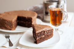 Chocolate cake with a cut piece and cup of tea Royalty Free Stock Photography