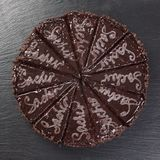 Chocolate cake cut in pieces, on black background. stock images