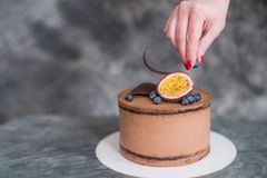 Chocolate cake on a dark background adorned with citrus. The confectioner`s hand holds a piece of cake on the patisserie Stock Images