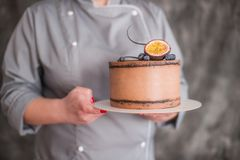 Chocolate cake on a dark background adorned with citrus. The confectioner`s hand holds a piece of cake on the patisserie Stock Photos