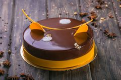 Chocolate cake with decor and biscuit, jelly, berries and mint on a wooden stand stock image