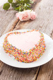 Chocolate cake decorate with pink cream butter and colorful suga Royalty Free Stock Image