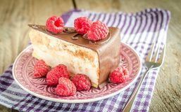Chocolate cake decorated with fresh raspberries. On the wooden table Royalty Free Stock Photo