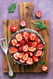 Chocolate cake decorated with fresh strawberries on a cutting board, purple background. Top view,flat lay stock image