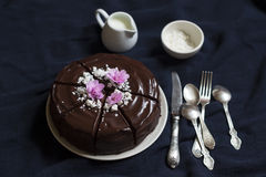 Chocolate cake decorated with meringue crumbs and violets Royalty Free Stock Image