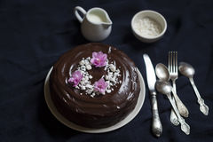 Chocolate cake decorated with meringue crumbs and violets Royalty Free Stock Photography