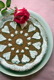 Chocolate cake decorated with sugar powder. On the table Stock Images
