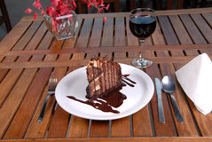 Chocolate cake desert ready to eat. Rich Chocolate filled cake with creamy chocolate all over it. Table setting flower in background with focus on dessert Stock Images