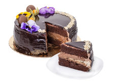 Chocolate cake with flowers, a piece on a plate. Royalty Free Stock Photography