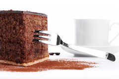 Chocolate cake with a fork and a cup of coffee in Royalty Free Stock Photography