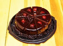 Chocolate cake with fresh cherries. Delicious chocolate cake sliced in portions with fresh cherries Royalty Free Stock Photography