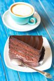 Chocolate cake and fresh coffee on blue wooden table. Stock Image